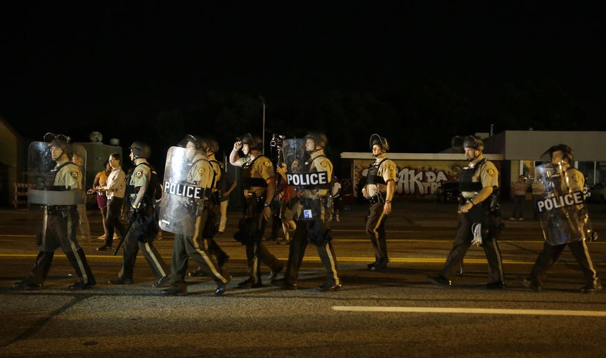 """Police walk around protesters as people gather along West Florissant Avenue in Ferguson, Mo., Tuesday, Aug. 11, 2015. The St. Louis suburb has seen demonstrations for days marking the anniversary of the death of 18-year-old Michael Brown, whose shooting death by a Ferguson police officer sparked a national """"Black Lives Matter"""" movement. Tuesday was the fifth consecutive night a crowd gathered on West Florissant, the thoroughfare that was the site of massive protests and rioting after Brown was killed. (AP Photo/Jeff Roberson)"""