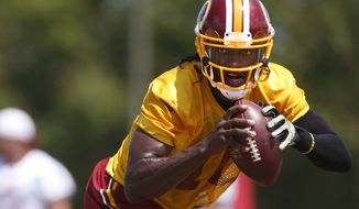 Washington Redskins quarterback Robert Griffin III rolls out during a drill at the NFL football team's training camp in Richmond, Va., on Tuesday, Aug. 11, 2015. (Dean Hoffmeyer/Richmond Times-Dispatch via AP)