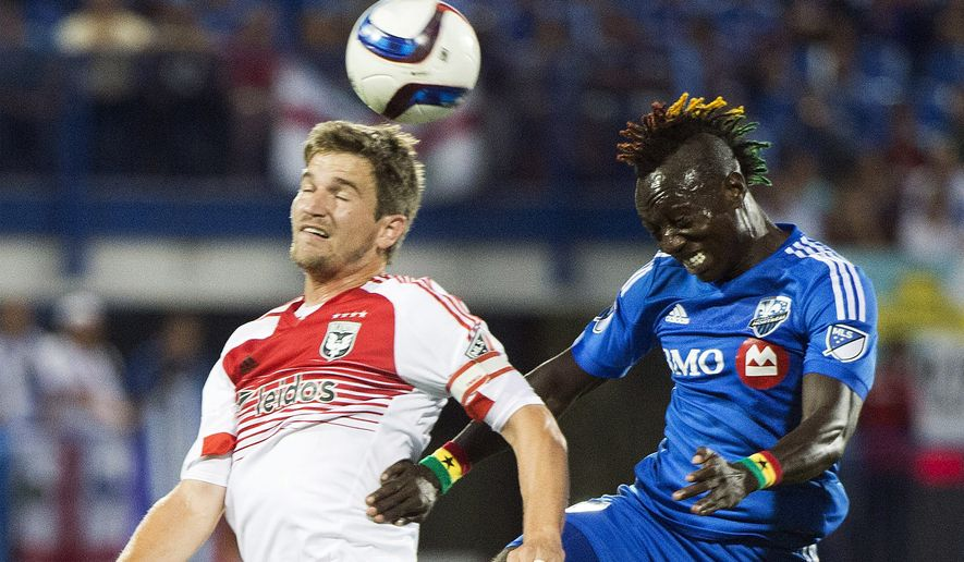 Montreal Impact's Dominic Oduro, right, challenges D.C. United's Bobby Boswell during first-half MLS soccer game action in Montreal, Saturday, Aug. 8, 2015. (Graham Hughes/The Canadian Press via AP)