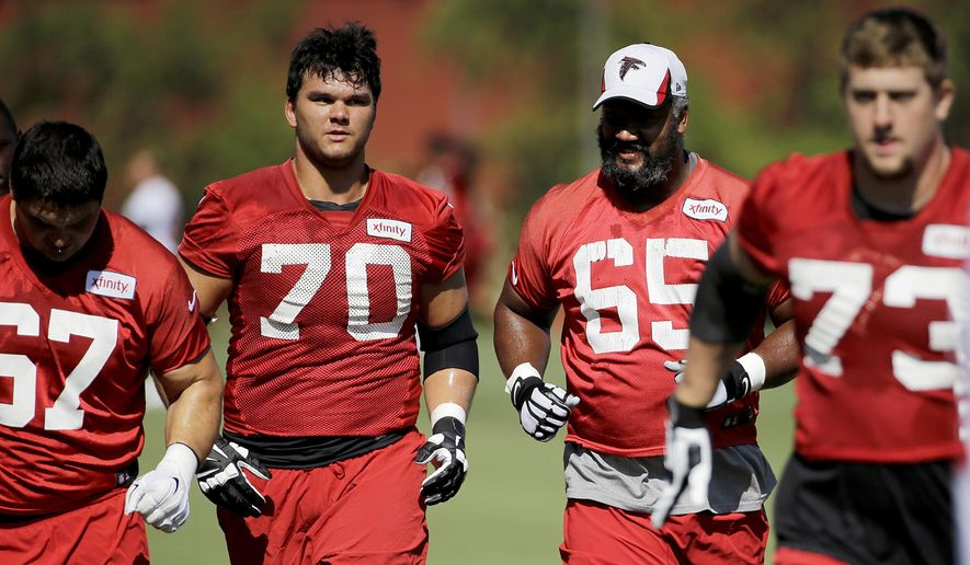 Atlanta Falcons tackle Jake Matthews (70) and center Chris Chester (65) run on the field during NFL football training camp Wednesday, Aug. 12, 2015, in Flowery Branch, Ga. The Falcons are preparing to showcase a new-look offensive line, including Matthews and Chester, in their preseason opener against Tennessee on Friday night. (AP Photo/David Goldman)