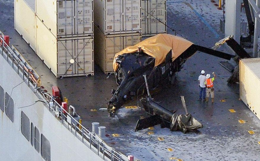 A yellow sheet covers a U.S. Army helicopter U-60 that crashed on the Navy cargo vessel USNS Red Cloud in the waters around 20 miles (30 kilometers) east of Japan's southern island of Okinawa Wednesday, Aug. 12, 2015. The helicopter crashed during a training mission while landing on the Navy ship, injuring several people and damaging the aircraft, officials said. (Ryosuke Uematsu/Kyodo News via AP) JAPAN OUT, CREDIT MANDATORY