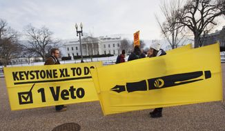 In this Feb. 24, 2015, file photo, Danny Ruthenberg-Marshall, left, with 350 DC, and Lindsey Halvorson, a student at American University, pick up their signs after attending gathering with other opponents of Keystone XL oil pipeline in support of a veto of the legislation outside the White House in Washington. (AP Photo/Jacquelyn Martin, File)