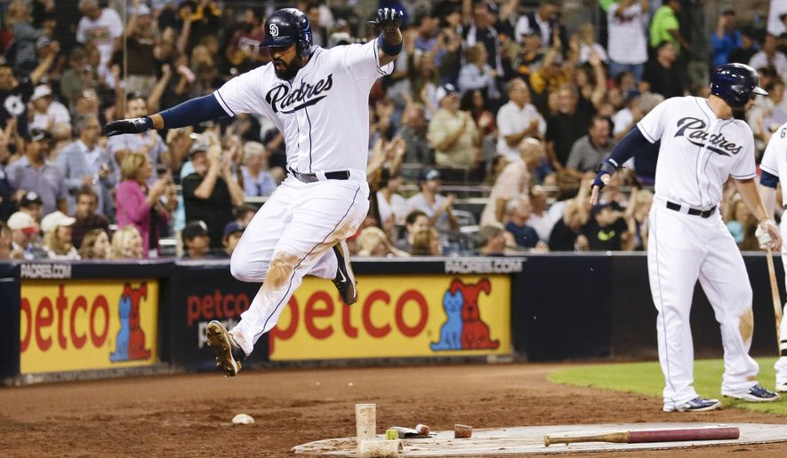 San Diego Padres' Matt Kemp, left, leaps after scoring against the Cincinnati Reds during the third inning of a baseball game Tuesday, Aug. 11, 2015, in San Diego. (AP Photo/Gregory Bull)