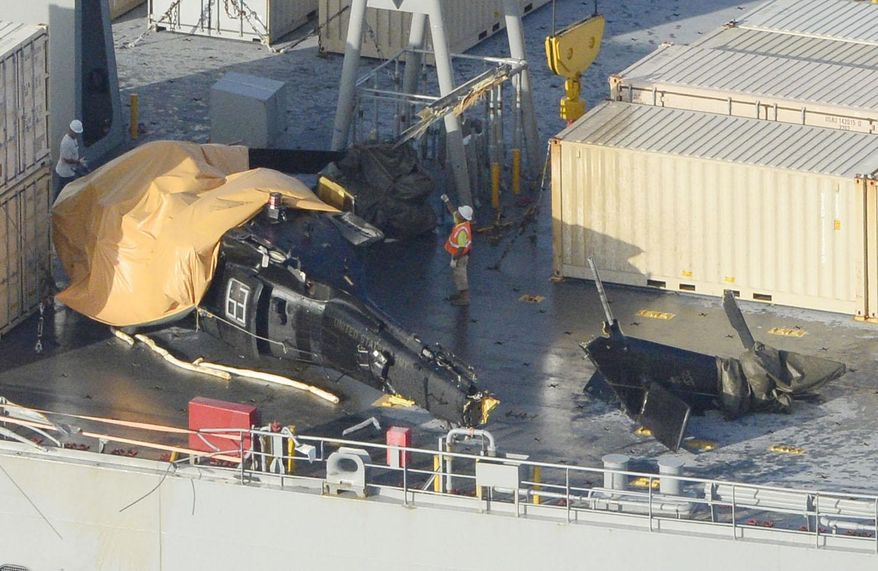 A yellow sheet covers a U.S. Army helicopter U-60 that crashed on the Navy cargo vessel USNS Red Cloud in the waters around 20 miles (30 kilometers) east of Japan's southern island of Okinawa Wednesday, Aug. 12, 2015. The helicopter crashed during a training mission while landing on the Navy ship, injuring several people and damaging the aircraft, officials said. (Ryosuke Uematsu/Kyodo News via AP)