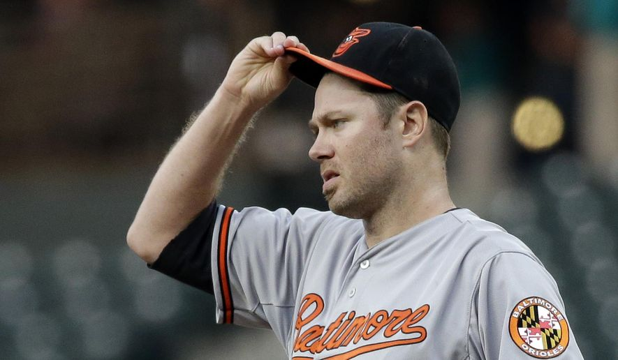 Baltimore Orioles starting pitcher Chris Tillman adjusts his cap after giving up three hits in a row to the Seattle Mariners in the first inning of a baseball game, Tuesday, Aug. 11, 2015, in Seattle. (AP Photo/Elaine Thompson)