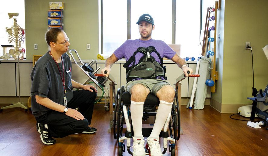 FOR RELEASE SATURDAY, AUGUST 15, 2015, AT 12:01 A.M. MDT.  - This photo taken Aug. 7, 2015, shows Mike Jones using a strength machine during a physical therapy session with Saint Alphonsus Regional Medical Center Physical Therapy Aide Todd McCarty as at left. Jones is going through occupation and physical therapy following a near-fatal collision between his bicycle and a motorcyclist. His legs are paralyzed, but they're working at Saint Alphonsus Regional Medical Center to get his upper body strengthened so he can be as independent as possible and go back to work. Mike works at Boise Cascade, and the folks there have got the place ready for him to come back.  (Kyle Green/Idaho Statesman via AP)
