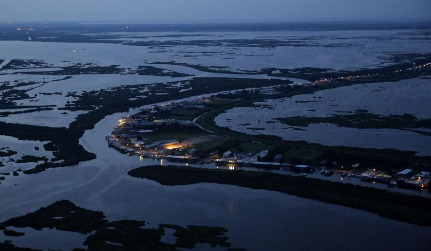 This aerial photo shows Delacroix Island surrounded by fragmenting and eroding marshland and coastal waters in St. Bernard Parish, La., on Tuesday, Aug. 11, 2015. The shrinking fishing community lies outside the the New Orleans area storm risk reduction system and is vulnerable to potential future storm surges. (AP Photo/Gerald Herbert)