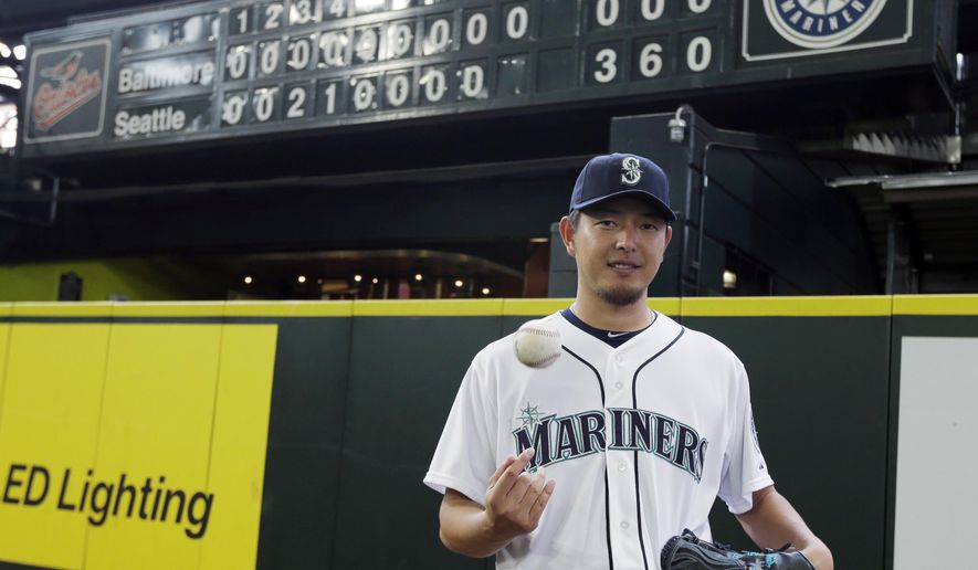 Seattle Mariners starting pitcher Hisashi Iwakuma tosses a baseball as he poses for a photo in front of the manual scoreboard at Safeco Field after he threw a no-hitter against the Baltimore Orioles in a baseball game Wednesday, Aug. 12, 2015, in Seattle. The Mariners won 3-0. (AP Photo/Ted S. Warren)