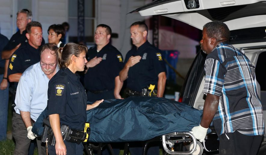 The body of Falco, a Toledo Police dog that was shot and killed, is brought out of a home on Earl Street early Wednesday, Aug. 13, 2015, in Toledo, Ohio.  Authorities say the police dog chasing two suspected car thieves was fatally shot, and one suspect was found dead after a standoff in Ohio.  (Jeremy Wadsworth/The Blade via AP)  MANDATORY CREDIT; MAGS OUT; NO SALES; TV OUT; SENTINEL-TRIBUNE OUT; MONROE EVENING NEWS OUT; TOLEDO FREE PRESS OUT