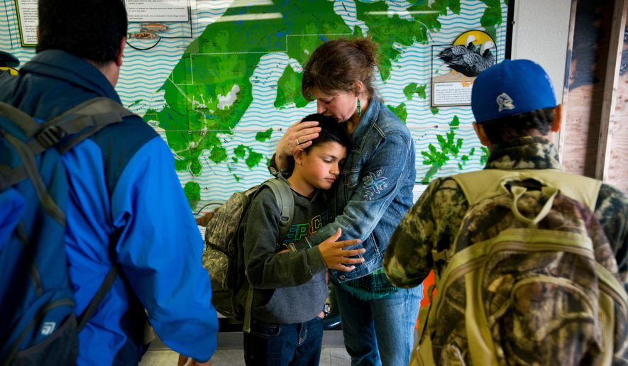 Sandy King hugs her son Matt Lopez, 12, before he boards a plane to move from Cold Bay on July 17, 2015. Matt's father Jorge Lopez, left, and brother, Zenny, right, are moving to California. King planned to join them there soon, she said. Since the Cold Bay school closed at the end of the 2014-15 school year, several residents have moved away or are planning to relocate soon. (Marc Lester/Alaska Dispatch News via AP)