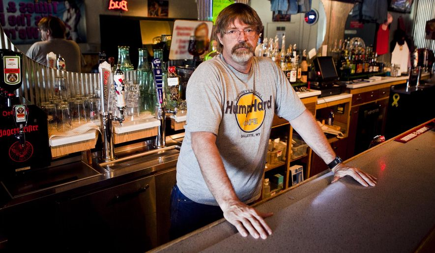 "In this Wednesday, Aug. 12, 2015 photo, Shotgun Willies owner Aaron Johnson poses behind his bar in Rapid City, S.D. The strip club is closing after spending much of its 31-year history at odds with religious groups and local officials. ""We'll be out of here by September 1. We're done,"" Johnson told the Rapid City Journal this week. (Sean Ryan/Rapid City Journal via AP) TV OUT; MANDATORY CREDIT"