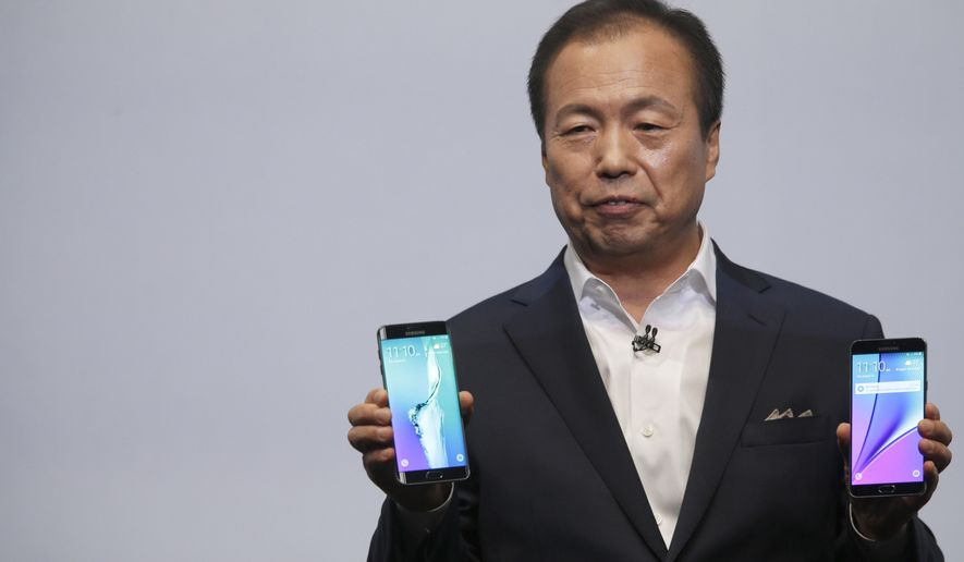 JK Shin, president and CEO of Samsung Electronics, holds the Samsung Galaxy S6 Edge Plus, left, and the Samsung Galaxy Note 5 during a presentation, Thursday, Aug. 13, 2015, at Lincoln Center in New York. (AP Photo/Mary Altaffer)