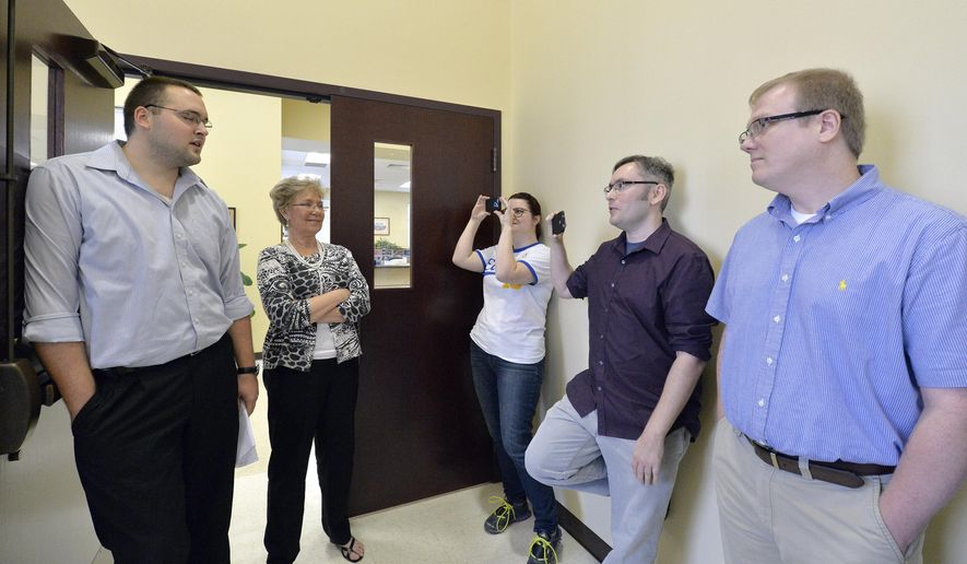 CORRECTS TO SAY THAT THE CLERK'S OFFICE WILL NOT BE ISSUING ANY MARRIAGE LICENSES, REGARDLESS OF WHETHER STRAIGHT OR SAME-SEX - Rowan County clerks Nathan Davis, left, and Roberta Earley, second left, inform David Ermold, right, and David Moore, second from right, that the county clerk's office will not be issuing marriage licenses to any couple, in defiance of an order from a federal judge, in Morehead, Ky., Thursday, Aug. 13, 2015. Rowan County Clerk Kim Davis has already filed a notice of appeal and plans to request a stay on the ruling. (AP Photo/Timothy D. Easley)