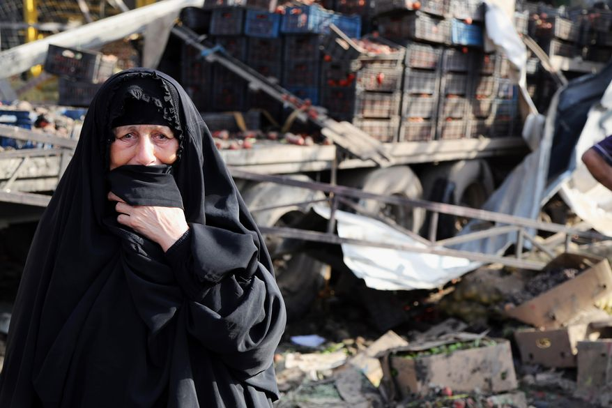 An Iraqi woman grieves at the scene of a bomb attack in Jameela market in the Iraqi capital's crowded Sadr City neighborhood Baghdad, Iraq, Thursday, Aug. 13, 2015. A massive truck bomb ripped through a popular Baghdad food market in a predominantly Shiite neighborhood in the early morning hours on Thursday, killing dozens of people, police officials said. (AP Photo/Karim Kadim)