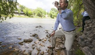 In this Tuesday, Aug. 11, 2015 photo, Colorado Gov. John Hickenlooper drinks water straight from the Animas River  in Durango, Colo., to get an update about the blowout from Gold King Mine. The water was treated with an iodine tablet before he drank it, to kill any giardia. (Shaun Stanley/The Durango Herald via AP) MANDATORY CREDIT