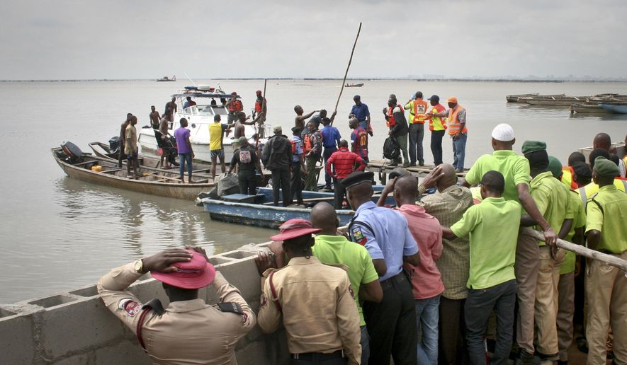 "Marine police, fishermen and other rescuers assist with recovering the bodies of two crew members, after a helicopter flying from an offshore oil rig plunged Wednesday afternoon into a lagoon, in Nigeria's commercial capital Lagos on Thursday, Aug. 13, 2015. The two bodies recovered on Thursday from the submerged aircraft were those of Capt. Joseph ""Jay"" Wyatt of Oklahoma and First Officer Peter Bellow of Nigeria, according to the helicopter's owner, Bristow Group of Houston, Texas, and were among six killed when the helicopter crashed. (AP Photo/Caelainn Hogan)"