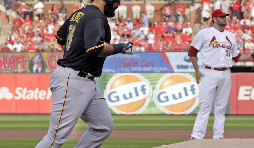 Pittsburgh Pirates' Pedro Alvarez, left, circles the bases as St. Louis Cardinals starting pitcher Lance Lynn looks on, after Alvarez hit a two-run home run in the first inning of a baseball game, Thursday, Aug. 13, 2015, in St. Louis. (AP Photo/Tom Gannam)