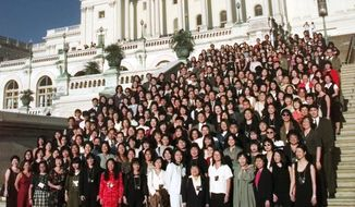 Korean adoptees pose for a photograph on the steps of the Capitol Friday, Sept. 10, 1999, in Washington. More than 400 Korean adoptees gathered for the first time, many of them the abandoned children of U.S. servicemen and Korean women. (AP Photo/Pablo Martinez Monsivais)