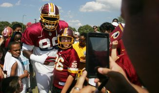 Washington Redskins defensive tackle Ricky Jean Francois takes a photo with Sam Byrne, 12, of Chesterfield, Va., during the team's NFL football training camp in Richmond, Va., Monday, Aug. 3, 2015. (AP Photo/Jason Hirschfeld)