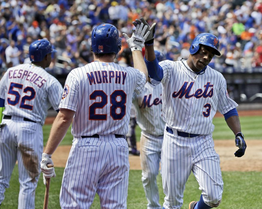 New York Mets' Curtis Granderson, right, celebrates his home run with Daniel Murphy, center, and Yoenis Cespedes (52) during the fourth inning of a baseball game against the Colorado Rockies at Citi Field, Thursday, Aug. 13, 2015, in New York. (AP Photo/Seth Wenig)