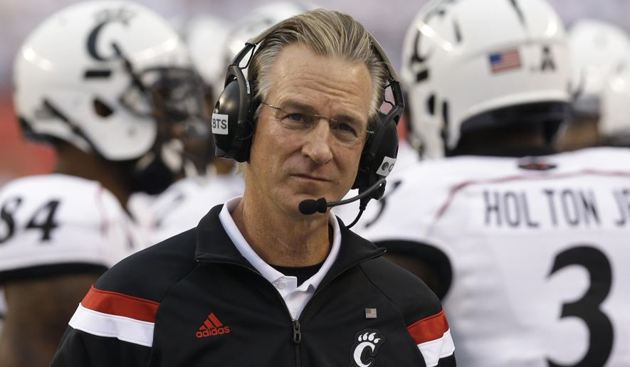 FILE - In this Sept. 12, 2014, file photo, Cincinnati head coach Tommy Tuberville works on the sidelines during the first half of an NCAA college football game against Toledo in Cincinnati. Tuberville's Bearcats  are favored to win the AAC this season ahead of Memphis. (AP Photo/Al Behrman, File)
