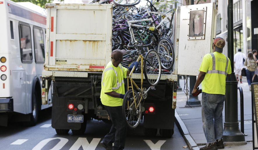 City workers toss an abandoned bike in the back of a truck Thursday, Aug. 13, 2015, in Philadelphia. The two-day sweep of abandoned bikes ending Thursday afternoon is an annual cleanup that's also part of the city's preparations for the pope's scheduled visit. A spokeswoman for the mayor's Office of Transportation and Utilities says 143 bikes are slated for removal. (AP Photo/Matt Rourke)