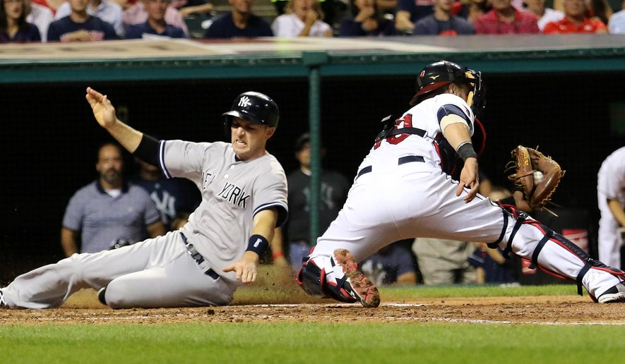 New York Yankees Stephen Drew scores on a single by Brad Gardner next to Cleveland Indians catcher Yan Gomes during the sixth inning of a baseball game Thursday, Aug. 13, 2015, in Cleveland. (AP Photo/Aaron Josefczyk)