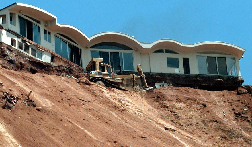 FILE - In this June 25, 1998 file photo, a Caltrans bulldozer terraces a sliding hillside below the condemned home above Pacific Coast Highway near Las Flores Canyon Road in Malibu, Calif. The home and at least one other at the top of the slide was scheduled for demolition. Federal meteorologists said Thursday that the current El Nino is already the second strongest on record for this time of year and could go down as one of the most potent weather changers of the past 65 years. The National Oceanic Atmospheric Administration recorded unusual warmth in the Pacific Ocean the last three months. El Nino is a heating of the equatorial Pacific that changes weather worldwide, mostly affecting the United States in winter.  (AP Photo/Reed Saxon, File)