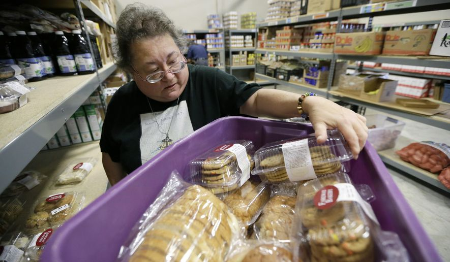 In this July 29, 2015 photo, volunteer Peggy Bragg, of Des Moines, Iowa, unloads donated baked goods at the Des Moines Area Religious Council food pantry in Des Moines, Iowa. Food banks across the country are seeing surging demand for free groceries despite a growing economy and steadily declining unemployment rate, leading some charities to reduce the amount of food they offer each family. (AP Photo/Charlie Neibergall)