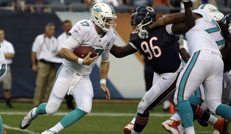 Miami Dolphins quarterback Ryan Tannehill (17) scrambles past Chicago Bears defensive tackle Jarvis Jenkins (96) to pick up a first down in the first half of an NFL preseason football game in Chicago, Thursday, Aug. 13, 2015. (AP Photo/Nam Y. Huh)