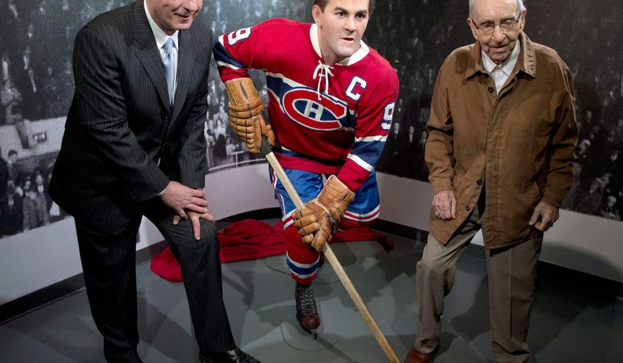 """FILE - In this April 10, 2014, file photo, former Montreal Canadiens Guy Lafleur, left, and Bob Fillion, right, pose with a wax statue of Maurice """"Rocket"""" Richard at the unveiling at the Montreal Canadiens Hall of Fame in Montreal. Fillion, who won the Stanley Cup with the Canadiens in 1944 and 1946, has died, the team's alumni association said Thursday, Aug. 13, 2015. He was 94.  (AP Photo/The Canadian Press, Ryan Remiorz, File)"""