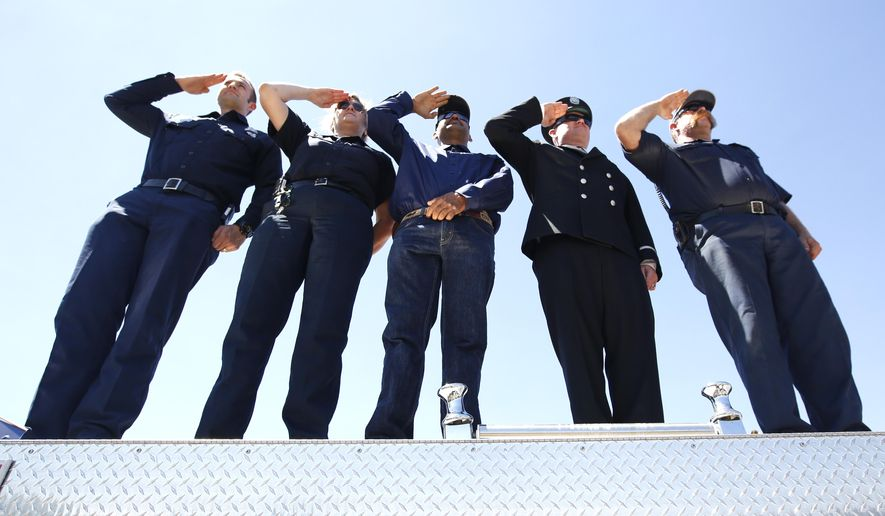 Firefighters, from left, Shawn Kellogg,  Leah Yaws, Tino Meza, John Ferry, and Michael Weidert salute as a procession of vehicles from various firefighting and law enforcement agencies escorting the body of U.S. Forest Service firefighter Michael Hallenbeck, passes through Placerville, Calif. Thursday, Aug. 13, 2015. Hallenbeck, 21, died from injuries after a tree fell on him while battling the Sierra Fire near South Lake Tahoe, Saturday.  Private memorial services are planned for Saturday, Aug. 15.(AP Photo/Rich Pedroncelli)