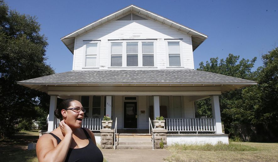 ADVANCE FOR SUNDAY AUG. 16 - In this Tuesday, Aug. 4, 2014 photo, homeowner April McDermott looks down the street while standing in front of her two-story 1902 Victorian Folk home in Marlin, Texas. The McDermott's have launched an essay contest to sell their 4,500 square- foot home  with the writer of the winning entry paying $1 to purchase the property. The only catch is a potential home buyers must submit a nonrefundable $100 fee with their essay in order to be considered for the contest. (Rod Aydelotte/Waco Tribune Herald, via AP) MANDATORY CREDIT