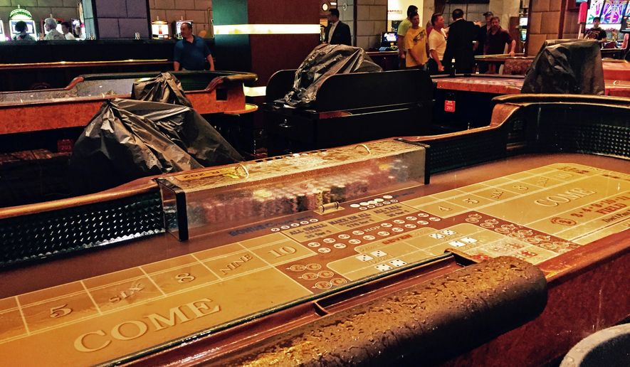 This photo provided by the Golden Nugget Las Vegas shows water-soaked craps tables, temporarily out of commission due to rain leaking through the casino roof, as an intense thunderstorm swept over Las Vegas, Thursday, Aug. 13, 2015. Multiple lightning strikes pounded the area and power outages were reported throughout much of the Las Vegas valley. (Golden Nugget Las Vegas via AP)