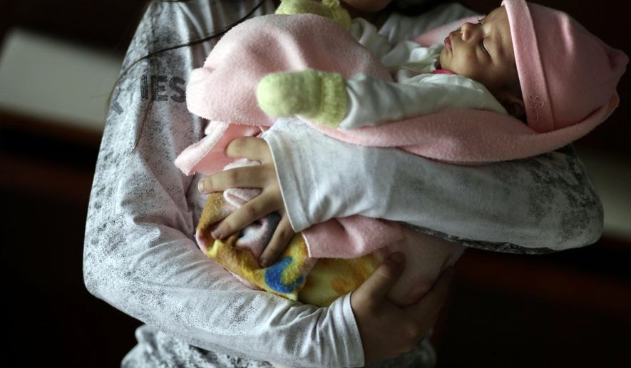 FILE - In this May 14, 2015 file photo, a 13-year-old girl holds her one-month-old baby at a shelter for troubled children in Ciudad del Este, Paraguay. The girl said she was raped by her stepfather from the time she was 10 and became pregnant when she was 12. Another pregnant girl, age 11, whose case drew international scorn when Paraguay's government denied her an abortion, gave birth on Thursday, Aug. 13, 2015. The girl was allegedly raped and impregnated by her stepfather when she was 10. In Paraguay, abortion is banned except when the mother's life is in danger. (AP Photo/Jorge Saenz, File)