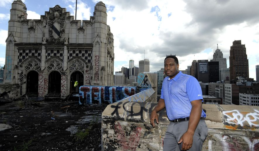 In this Tuesday, Aug. 11, 2015 photo, Eric Means, president of the Means Group and a managing member of Metropolitan Development Partners, poses on the rooftop near the proposed penthouse of the Metropolitan building in downtown Detroit. The 15-story building, which was built in 1925 and has been vacant for decades, is expected to reopen as an extended-stay hotel with ground-floor retail following a proposed $32 million renovation. (Todd McInturf/Detroit News via AP)