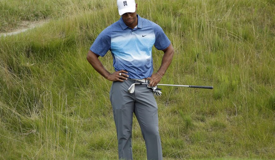 Tiger Woods looks at his ball in the bunker on the 18th hole during the first round of the PGA Championship golf tournament Thursday, Aug. 13, 2015, at Whistling Straits in Haven, Wis. (AP Photo/Chris Carlson)