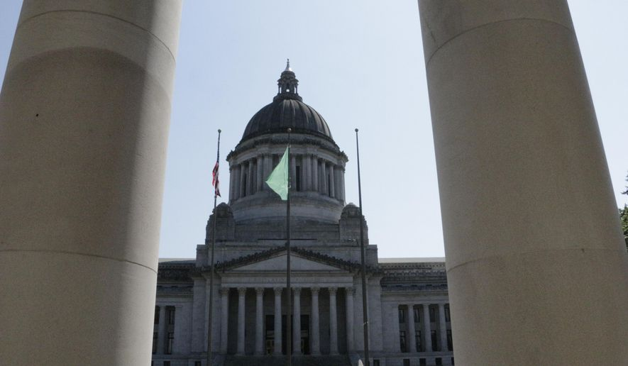 The Washington state Capitol is seen through the columns of the state Supreme Court on Thursday, Aug. 13, 2015, in Olympia, Wash. The court has issued sanctions of $100,000 a day against the state for its lack of progress on a plan to full fund basic education. (AP Photo/Rachel La Corte)