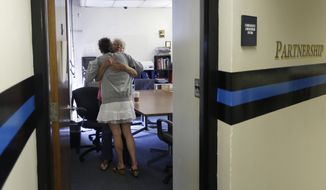 In this July 10, 2015, photo, volunteer Ruth Cote, facing, hugs a woman inside the police station in Gloucester, Mass., who has voluntarily come to the police for help kicking her heroin addiction. Gloucester is taking a novel approach to the war on drugs, making the police station a first stop for addicts on the road to recovery. Addicts can turn in their drugs to police, no questions asked, and officers, volunteers and trained clinicians help connect them with detox and treatment services. (AP Photo/Elise Amendola)