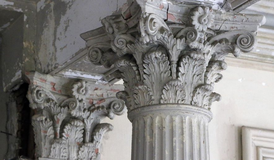 ADVANCE FOR WEEKEND EDITIONS AUG. 15-16 -In this Wednesday, July 15, 2015 photo ornately carved Corinthian columns show signs of cracking, peeling and other decay inside the front foyer of the Heck-Andrews House, at 309 North Blount Street in downtown Raleigh, N.C.. The State of North Carolina recently restored the outside of the Second Empire-style three story mansion built by industrialist Jonathan McGee Heck. The interior, however, is in a deteriorated state with crumbling plaster, fallen ceilings and a collapsing kitchen floor. The State of North Carolina is not sure if it wants to spend the money to restore the interior. (Harry Lynch/The News & Observer via AP) MANDATORY CREDIT