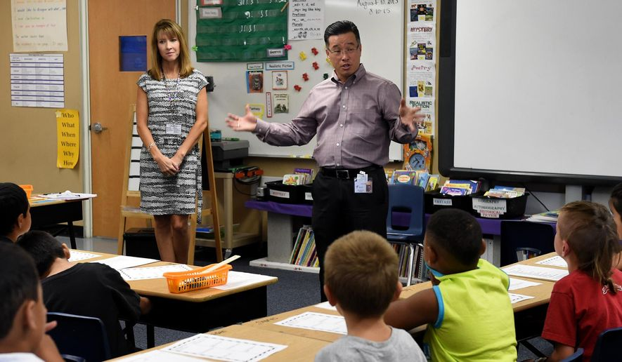 In this photo taken on Monday, Aug. 10, 2015, Libby Booth Elementary School principal Yuen Fong and vice principal Annalisa Walker, left, introduce themselves to a second grade class as the new principals at the school, in Reno, Nev. Both went to each classroom to introduce themselves and to tell students of the two basic rules at Libby Booth, which are keep bodies and objects to yourself, and use kind and encouraging words. (Andy Barron/The Reno Gazette-Journal via AP)  NO SALES; NEVADA APPEAL OUT; SOUTH RENO WEEKLY OUT; MANDATORY CREDIT