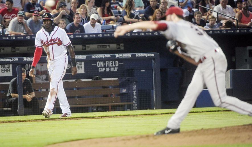 Atlanta Braves' Cameron Maybin watches the pitch of Arizona Diamondbacks' Robbie Ray, right, after hitting an RBI triple during the third inning of a baseball game, Friday, Aug. 14, 2015, in Atlanta. (AP Photo/John Amis)