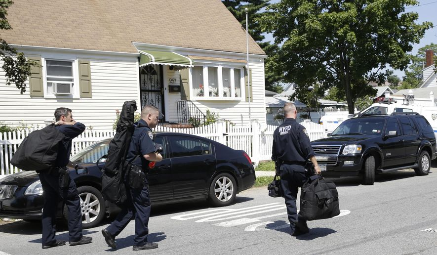New York City Police Department Emergency Service members carry their gear as they leave the scene of a standoff, Friday, Aug. 14, 2015, in the Staten Island borough of New York. Garland Tyree, a high-ranking member of the Bloods street gang who was to be arrested on parole violations when he shot a firefighter responding to a call of smoke coming from his girlfriend's home, died Friday in a gunfight with police after a six-hour standoff, two police officials said.  (AP Photo/Mary Altaffer)
