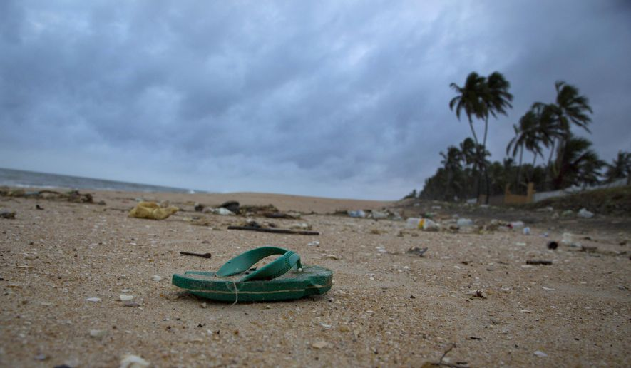 In this Aug. 13, 2015 photo, a sandal lies among other debris washed ashore on the Indian Ocean beach in Uswetakeiyawa, north of Colombo, Sri Lanka. (AP Photo/Gemunu Amarasinghe)
