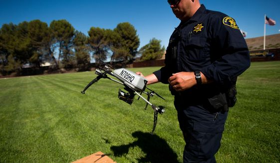 Alameda County Sheriff's Deputy Dave Durbin prepares to fly a drone during a demonstration of a search and rescue operation on Friday, Aug. 14, 2015, in Dublin, Calif. As law enforcement joins the ranks of hobbyists sending drones into California skies, civil liberties advocates are raising the specter of unchecked police surveillance and state lawmakers are drafting limits. (AP Photo/Noah Berger)