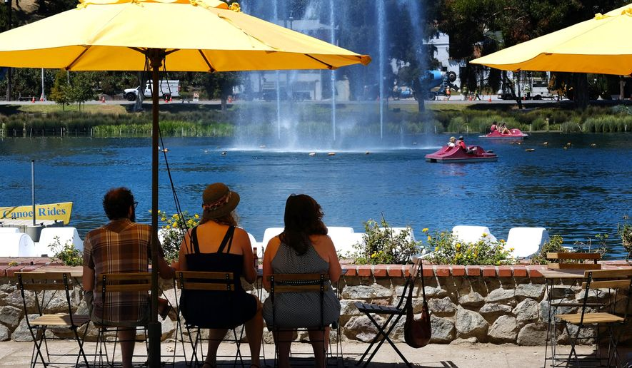 Visitors to Echo Park Lake near downtown Los Angeles shade themselves under an umbrella as paddle boats keep close to a large fountain to keep cool on Friday, Aug. 14, 2015. The National Weather Service says Southern California's sharp warming trend will build into the weekend, with above-normal temperatures in many areas. Forecasters say the hottest conditions will be Friday through Sunday. Valley and desert temperatures will range from 100 to108 degrees, with highs from 85 to 95 elsewhere. (AP Photo/Richard Vogel)
