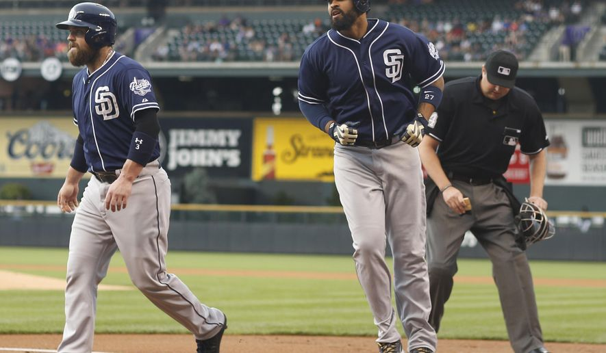 San Diego Padres' Matt Kemp, center, crosses home plate after hitting a two-run home run to drive in teammate Derek Norris, left, as home plate umpire Lance Barrett cleans off the plate against the Colorado Rockies in the first inning of a baseball game Friday, Aug. 14, 2015, in Denver. (AP Photo/David Zalubowski)