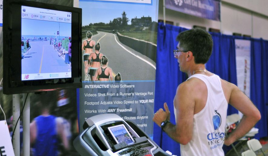 In this Thursday, Aug. 13, 2015 photo, Joe Ciavattone, an employee of Outside Interactive, demonstrates the company's virtual race technology at the New Balance Falmouth Road Race expo in Falmouth, Mass. The company is partnering with the race to let runners compete on a treadmill virtually from anywhere while watching video footage of the actual 7-mile course. (AP Photo/Collin Binkley)
