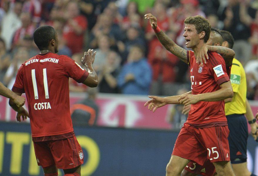 Bayern's Thomas Mueller, right, celebrates with his teammate Douglas Costa after scoring his side's fourth goal during the German Bundesliga soccer match between FC Bayern Munich and Hamburger SV in Munich, southern Germany, Friday, Aug. 14, 2015. (AP Photo/Kerstin Joensson)
