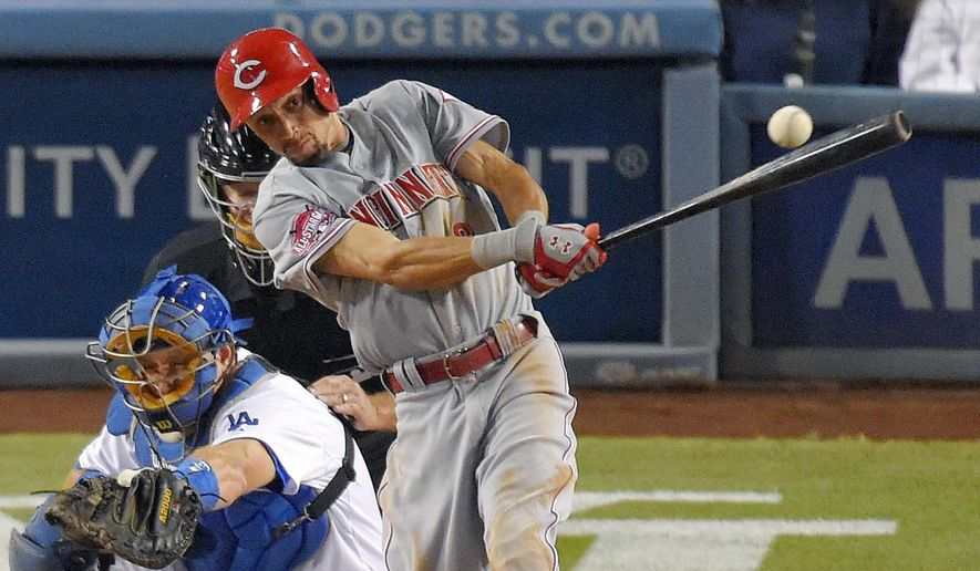 Cincinnati Reds' Billy Hamilton hits a single as Los Angeles Dodgers catcher A.J. Ellis watches during the sixth inning of a baseball game, Thursday, Aug. 13, 2015, in Los Angeles. (AP Photo/Mark J. Terrill)